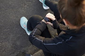 Young Woman Checks Activity Tracker During Outdoor Exercise