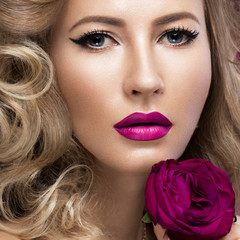 Beautiful blonde in a Hollywood manner with curls, pink lips. Beauty face.