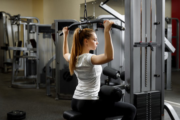 A young girl training her body alone in a gym. Training for strength of the back muscles