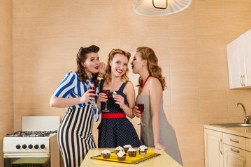 three girl friends in retro pin up style dresses are drinking red wine and eating muffins in the kitchen. Hen party at home