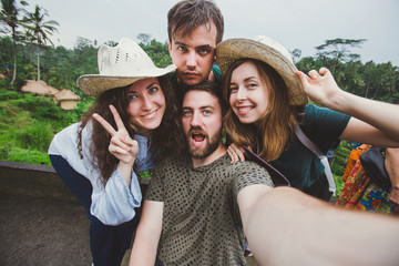A group of friends take selfie for travel blog near rice fields in Ubud in Bali while trip around the world.