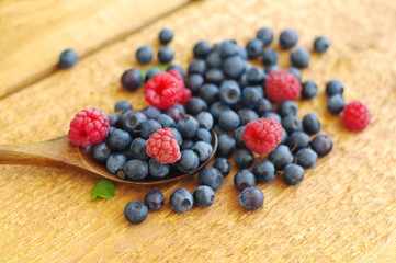 Juicy mature berries of bilberry and raspberry in in a wooden spoon on a wooden surface.