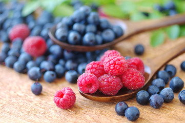 Juicy mature berries of bilberry and raspberry in in a wooden spoons on a wooden surface.