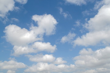 blue sky is covered by white clouds and raincloud