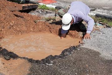 Male workers repair pipe water main broken, tube underground water on road.