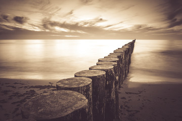 Coast with piles during sunset, long exposure blurring water.Vintage photo of baltic, Poland. Wall mural