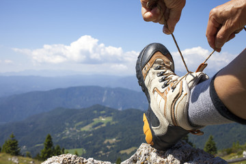 Hiker tying boot laces on rock, high in the mountains, space for text