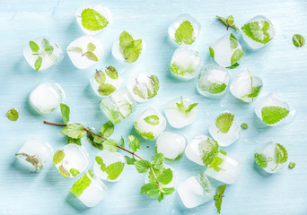 Ice cubes with frozen mint leaves inside on blue Turquoise background