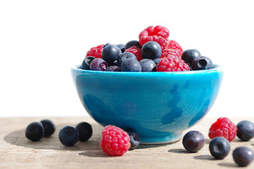 Juicy mature berries of raspberry and bilberry in a small blue bowl on a wooden surface.
