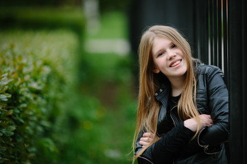 portrait of beautiful smiling cool girl posing in black leather jacket over grunge fence