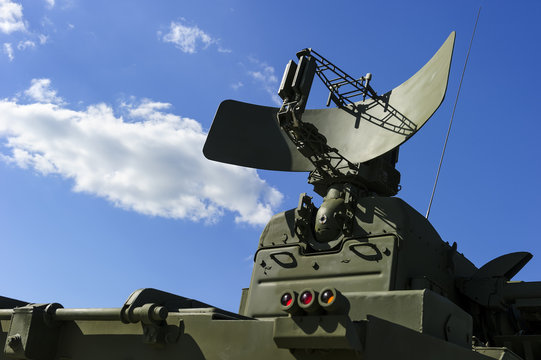 Air defense radar of military mobile mighty missile launcher system of green color, modern army industry, white cloud and blue sky on background