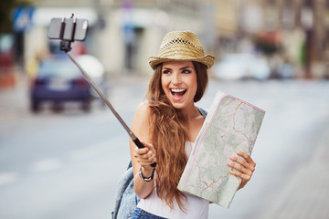 Happy woman taking photo on vacation with selfie stick
