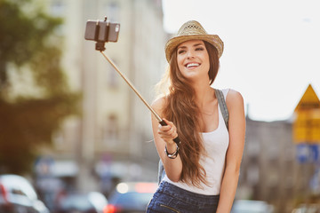Woman on vacation taking photo with selfie stick