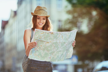 Attractive young woman reading map in the city
