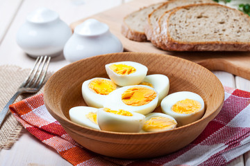 Half-boiled eggs in a wooden bowl.