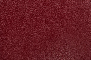Dark red leather texture background. Closeup photo.