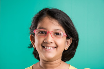 Happy little indian girl smiling while wearing glasses, green background, indian small girl wearing glass, asian small girl and glasses, 10 year old girl, extreme closeup or close up
