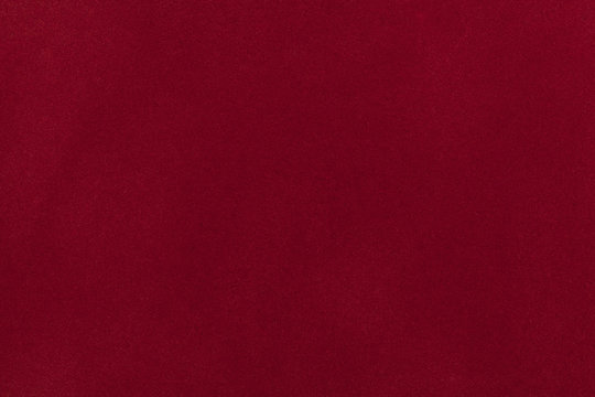 Dark red suede fabric closeup. Velvet texture.