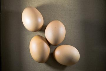 Fresh chicken eggs on a brown background.
