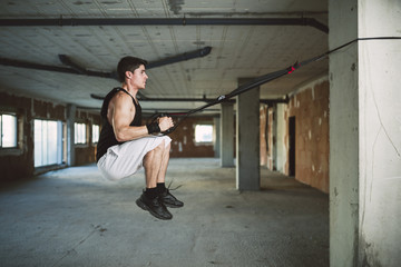 Young man exercising suspension training trx, jumping
