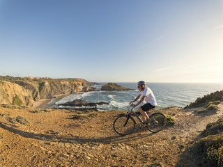 Portugal, Senior man mountain biking at the sea