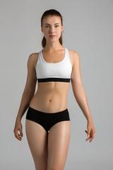 Female fitness Model posing on grey