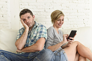 attractive couple at home couch happy woman internet addict on mobile phone ignoring sad husband