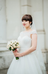 Beautiful smiling bride portrait near architecture with flowers