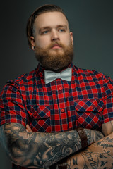 Tattooed bearded unformal male in red shirt and grey bow tie.