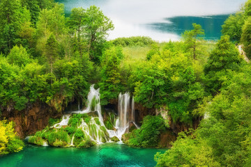 Plitvice Lakes National Park amazing emerald lakes and waterfalls, surrounded by forests in Croatia, nature background suitable for wallpaper or guide book