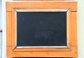 Blackboard with broad wooden frame mounted to a wall