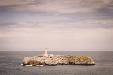 Lighthouse over rocks on an island, Spain