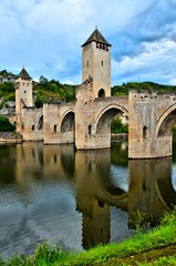 Medieval stone bridge at Cahors, France with watch towers and river reflections