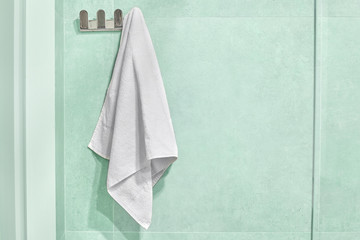White towel hanging on a wall in bathroom