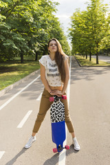 Trendy young women leaning on a longboard is on the path in the park. Lifestyle outdoor