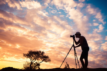 The art of photography. Male photographer taking photos of a beautiful sunset.