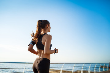 Picture of young attractive fitness girl jogging with sea on background