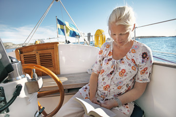 Woman reading book while travelling in boat