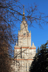 Sunny view of Moscow State University main building with reflections in windows through autumn tree branches
