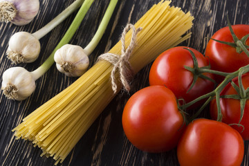 Raw pasta and ingredients with tomatoes , garlic.