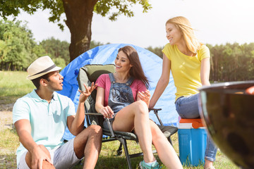 Cheerful young camping group having rest