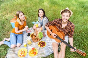 Cute friends making picnic in nature