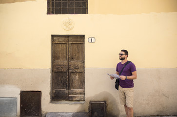 Tourist with map standing by old building