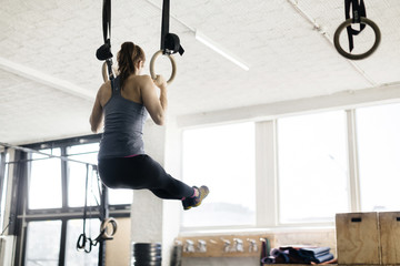 Young woman exercising on gymnastic rings in gym