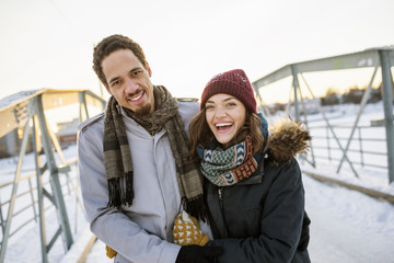 Sweden, Vasterbotten, Umea, Young couple on footbridge in winter