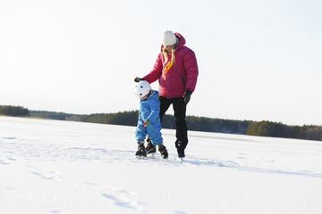 Sweden, Sodermanland, Jarna, Mother teaching son (2-3) ice skating on frozen lake