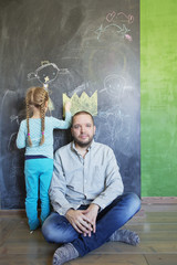 Finland, Girl (4-5) standing by father and drawing on chalkboard