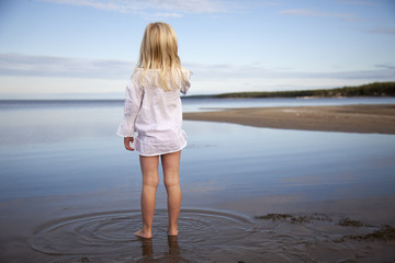 Rear view of girl standing in sea