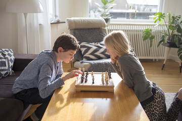 Sibling playing chess while sitting in living room