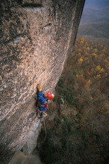 Male rock climber aid climbing on Looking Glass Rock, North Carolina.